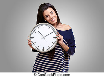portrait of young woman holding clock against a grey background