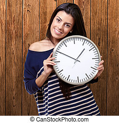 portrait of young woman holding clock against a wooden wall