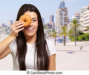 portrait of young woman holding donut in front of her eye against the beach