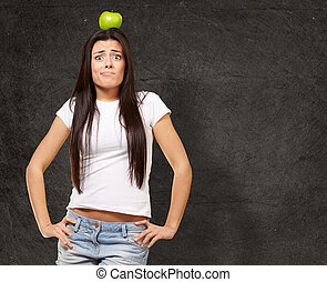 portrait of young woman holding green apple on her head against a grunge wall