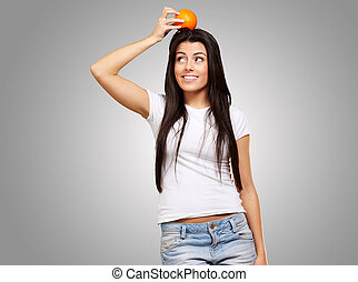 portrait of young woman holding orange on her head over grey