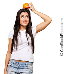 portrait of young woman holding orange on her head over white