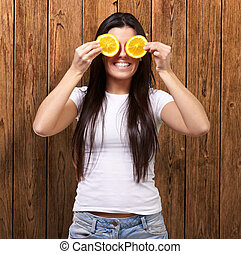 portrait of young woman holding orange slices in front of her eyes against a wooden wall