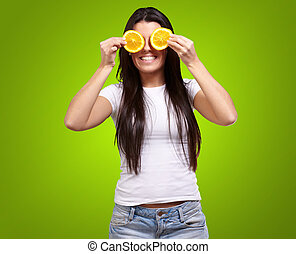 portrait of young woman holding orange slices in front of her eyes over green background