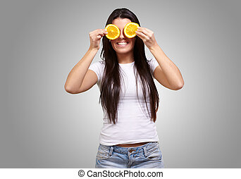 portrait of young woman holding orange slices in front of her eyes over grey background