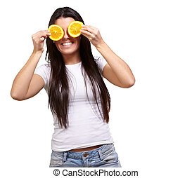 portrait of young woman holding orange slices in front of her eyes over white background