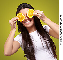 portrait of young woman holding orange slices in front of her eyes over yellow background