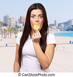 portrait of young woman holding potato chip on her mouth against a beach