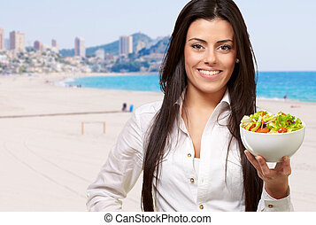 portrait of young woman holding salad against a beach