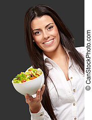 portrait of young woman holding salad over black