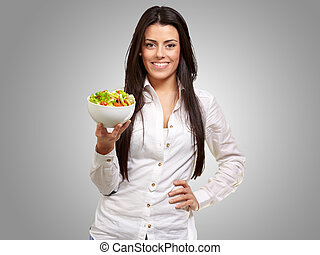 portrait of young woman holding salad over grey
