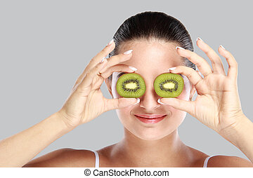 young woman holding slices of kiwi in front of her eye