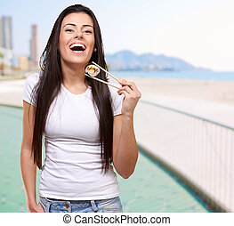 portrait of young woman holding sushi against a beach