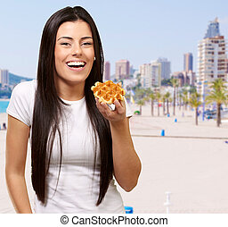 portrait of young woman holding waffle against a beach