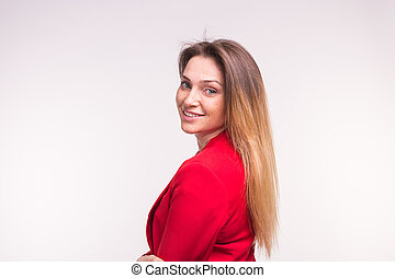 Portrait of young woman in a red suit posing on white background with copy space