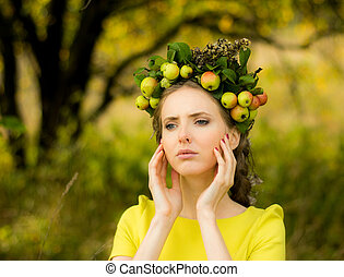 Portrait of young woman in apple garden