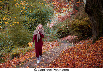 Portrait of young woman in autumn park