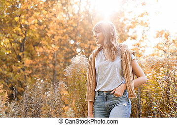 Portrait of young woman in autumn park. Trees with yellow foliage in the background, beautiful sunset light. Warm sweater on the shoulders