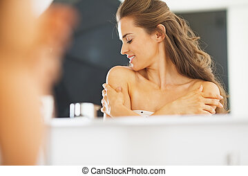 Portrait of young woman in bathroom happy with her skin ...