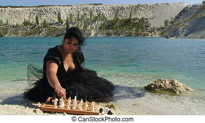 Portrait of Young Woman In Black Dress Playing Chess Near Lake
