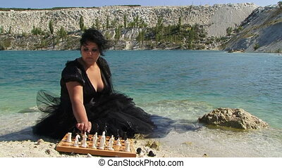 Portrait of Young Woman In Black Playing Chess