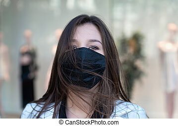 Portrait of young woman in black protective medical mask. Quarantine