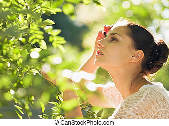 Portrait of young woman in foliage looking on copy space