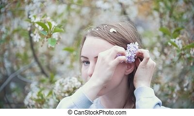 Portrait of young woman in garden - girl sticks a sprig of lilac in her hair