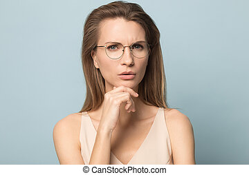 Portrait of young woman in glasses looking at camera