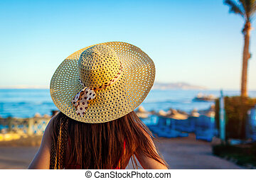 Portrait of young woman in hat walking on Red sea beach