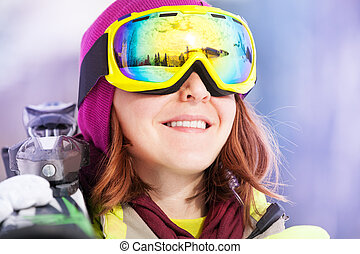 Portrait of young woman in mask holding ski