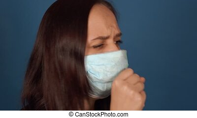 Portrait of young woman in medical mask coughing, being ...