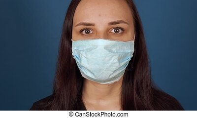 Portrait of young woman in medical mask on her face on blue ...
