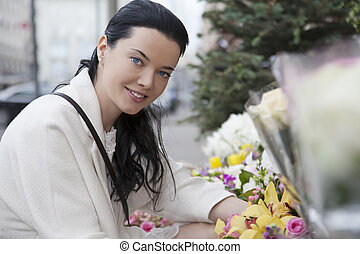 Portrait of young woman in outdoors flower-shop