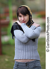 Portrait of young woman in park with a scarf on a head