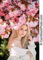 Portrait of young woman in park with blooming sakura trees.