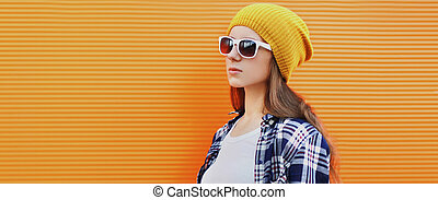 Portrait of young woman in profile looking away wearing a yellow hat over an orange background