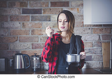 Portrait of young woman in red shirt at kitchen