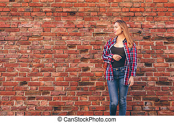 Portrait of young woman in shirt and jeans