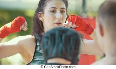 Portrait of young woman in sportswear at boxing workout in...