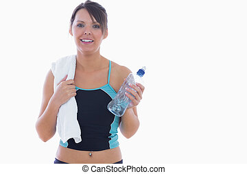 Portrait of young woman in sportswear holding towel around neck and water bottle over white background