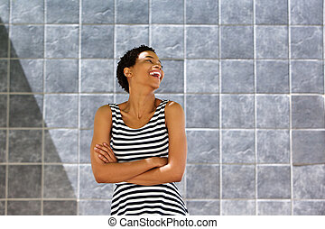 young woman in striped dress laughing against gray wall