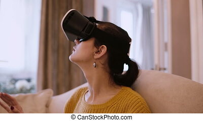 Portrait of young beautiful woman getting experience in virtual reality glasses sitting on the sofa at home. Female looking around in VR-headset.