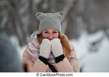Portrait of young woman in winter park standing on alley, smiling