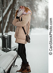 Portrait of young woman in winter park standing on alley, wrapped in a scarf near bench
