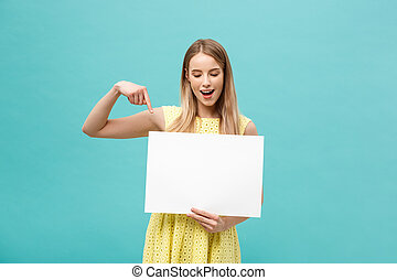 Portrait of young woman in yellow dress pointing finger at side white blank board. Isolated over Blue background.