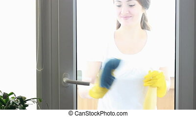 Portrait of young woman in yellow rubber gloves looks at camera smiling and washes windows and glass. The concept of cleaning, cleanliness.