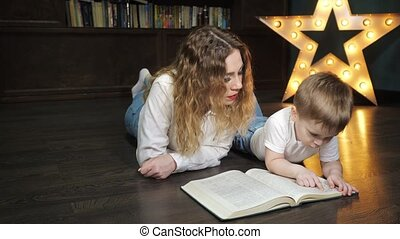 Portrait of young woman is reading a book with her little son.