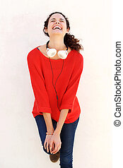 young woman laughing against white background with headphones