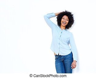 young woman laughing with hand in hair on white background